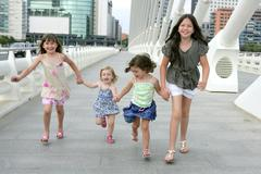 Four little girl group walking in the city Stock Photos
