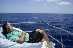 Stock Photo of Sailor senior man having a rest on summer boat