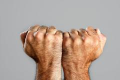 Hairy man fist closeup expression over gray - stock photo
