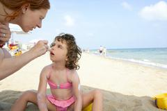 Daughter and mother on the beach sun screen moisture Stock Photos