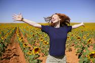 Happy redhead woman in sunflowers field Stock Photos