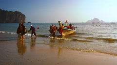 Tourists unloading bags from a longtail boat at Railay Beach in Thailand. Stock Footage