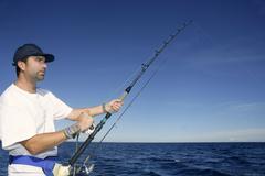 Angler fisherman trolling rod and reel fishing Stock Photos