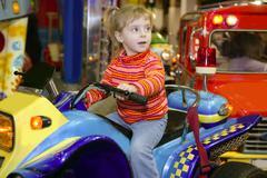 Blond little girl in funfair fairground attraction Kuvituskuvat