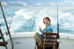 fisherwoman big game on boat chair ok sign - stock photo