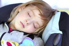 Little girl sleeping on children car safety seat Stock Photos