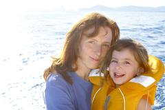 Mother and daughter safety vest backlight sea Stock Photos