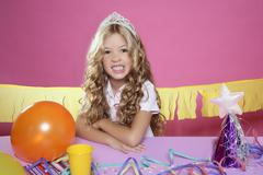 Stock Photo of bored little blond girl birthday party with candle cake