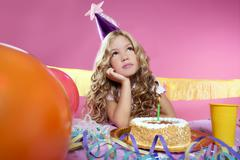 bored little blond girl birthday party with candle cake - stock photo