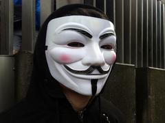 Anonymous group member wearing Guy Fawkes mask - stock photo