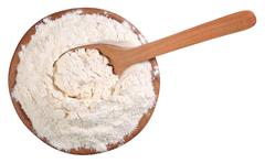 Top view of white flour in a wooden bowl with spoon on a white Stock Photos