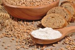 White flour in a wooden spoon, wheat and bread - stock photo