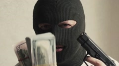 Man in a mask bandit aggressively shakes money and a gun Stock Footage