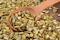 Cleared pumpkin seeds in a spoon - stock photo