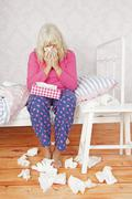 Girl on bed blowing nose - stock photo