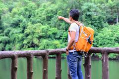 Man hiker in blue jean with orange backpack pointing and looking view of rive - stock photo