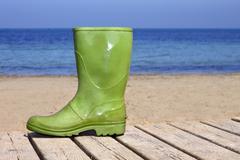 Green boot on beach unlucky fisherman metaphor Stock Photos