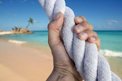 man hand grab grip adventure paradise beach rope - stock photo