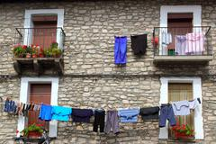 Clothes line hanging from stone wall houses - stock photo