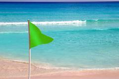 Green beach flag good beach weather - stock photo