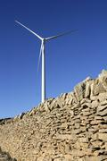 Electric windmills with a masonry rural wall Stock Photos