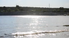 Water with small waves and far bank with knolls and forest Stock Footage