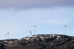 aerogenerator windmills on snow mountain - stock photo