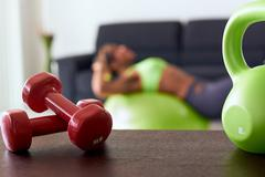 Home Fitness Red Weights On Table And Woman Training Abs Stock Photos
