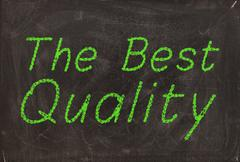 """""""The best quality"""" handwritten with green chalk on a blackboard - stock photo"""