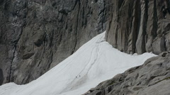 Stock Video Footage of Climbers crossing avalanche cone below alpine rock face Chamonix