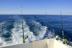 Fishing rod and reel on boat, fishing in blue ocean - stock photo