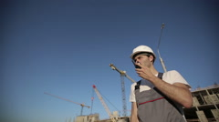Engineer builder using a walkie talkie giving instructions at construction site Stock Footage