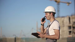 Stock Video Footage of Engineer builder using tablet and walkie talkie, giving instructions