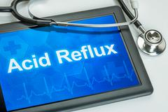Tablet with the diagnosis Acid Reflux on the display Stock Photos