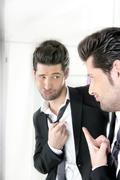 Stock Photo of Handsome man humor funny gesture in a mirror