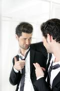 Handsome man humor funny gesture in a mirror - stock photo