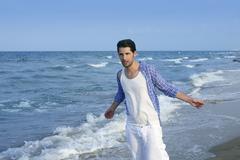 Mediterranean latin young man on beach - stock photo