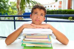 boy student teenager bored thinking with books - stock photo