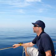 Stock Photo of Sailor man sailing boat blue calm ocean water