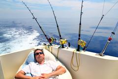 Stock Photo of Sailor man fishing resting in boat summer vacation