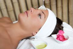 spa beauty facial treatment oil brush and flowers - stock photo