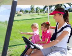 golf course family mother and daughters in buggy - stock photo