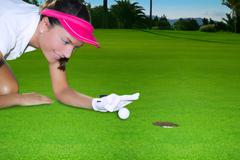 Golf green hole woman humor flicking hand a ball - stock photo