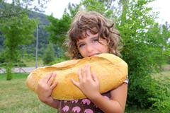 girl eating big bread humor size hungry child - stock photo