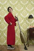 Bathrobe retro housewife woman vacuum cleaner - stock photo