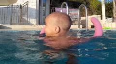 Toddler loses grip of water noodle and swims Stock Footage
