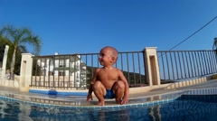 Stock Video Footage of Toddler sits on the edge of the swimming pool