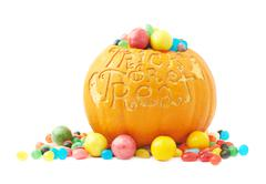 Trick or treat pumpkin filled with candy sweets - stock photo