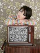 Retro pensive woman on vintage wooden tv 60s Stock Photos