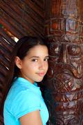 Latin mexican teen girl smile indian wood totem - stock photo